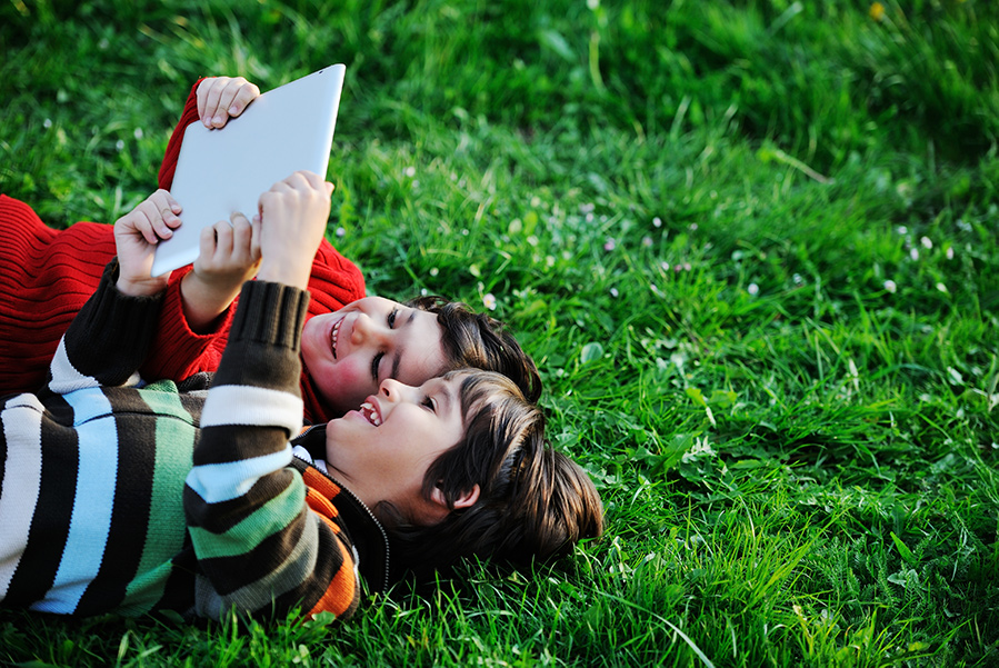 Kids using tablet outdoors